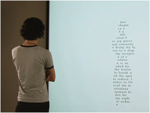 "Screen shot from ""Still Standing"" by Bruno Nadeau and Jason Edward Lewis. A picture of a man standing in front of a white screen and on the screen words take the shape of his body."