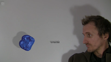 "Screen capture of ""Sound Seeker"" by David Jhave Johnston. A blond, white man, standing in front of a white wall, only visible from the shoulders and up. He is at the right corner of the picture looking at a blue matter that is floating in midair at the corner of the left side of the picture. The word ""crucial"" is in the middle of the man and the blue matter. Their shadows are reflected on the white wall (the man's, the matter's and the word's)."