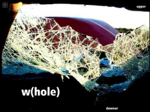 "Screen capture of ""Joyride"" by Judi Alston and Andy Campbell. Inside view of a shattered windshield after an apparent hard collision. Text: ""w(hole)"""