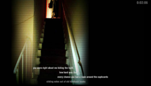 "Screen shot from ""The Flat"" by Andy Campbell. The picture is surrounded by darkness except for a viewable glance of a staircase and at the top there is someone waiting. The text is in white in front of the staircases and is impossible to view."