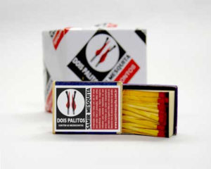 "Screen capture from ""Dois palitos"" (Two matchsticks) by Samir Mesquita. Photograph of an open matchbox standing upright on its side, bearing a logo of two burning matches. A larger box bearing the same logo as the matchbox is visible in the background. Text: ""dois palitos, Samir Mesquita"""